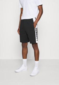 Lacoste - Jogginghose - noir/blanc